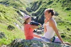 Mãe e filha que descansam na pedra grande na excursão do curso Imagens de Stock