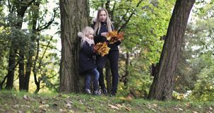 A mãe e a filha que descansam no outono estacionam video estoque