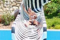 Mãe e filha que deslizam no aquapark imagens de stock