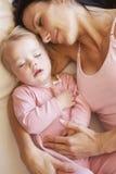 Mãe e filha que dormem na cama fotografia de stock