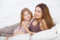 Mãe e filha que encontram-se em uma cama branca Imagem de Stock