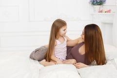 Mãe e filha que encontram-se em uma cama branca Imagem de Stock Royalty Free