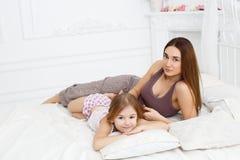 Mãe e filha que encontram-se em uma cama branca Fotos de Stock Royalty Free