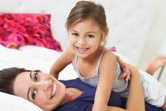 Mãe e filha que encontram-se na cama junto fotografia de stock