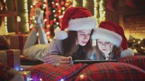 Mãe e filha que encontram-se na cama e para olhar a tabuleta nas decorações do Natal video estoque
