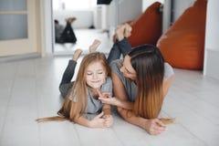 Mãe e filha que encontram-se no assoalho e no olhar em se Fotografia de Stock Royalty Free