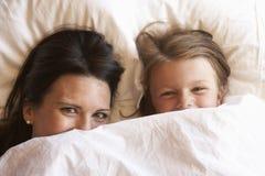 Mãe e filha que escondem sob o roupa de cama fotos de stock