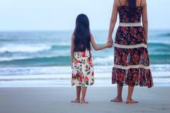 Mãe e filha que estão na praia fotos de stock