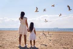 Mãe e filha que estão na praia imagem de stock