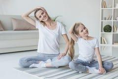 mãe e filha que esticam o pescoço antes de exercitar fotografia de stock royalty free