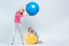 Mãe e filha que exercitam com bolas da aptidão fotos de stock royalty free
