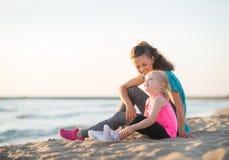 Mãe e filha que falam e que sentam-se na praia Foto de Stock