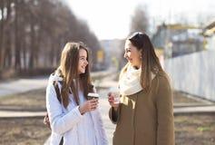 Mãe e filha que falam, sorriso de riso na rua, café bebendo em uns copos Fotos de Stock