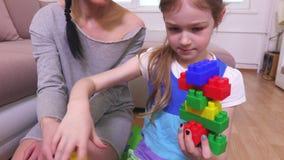 Mãe e filha que fazem a construção de tijolos do brinquedo vídeos de arquivo
