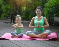 Mãe e filha que fazem a ioga praticando do exercício fora Imagens de Stock