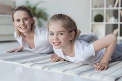 a mãe e a filha que felizes fazer empurra levantam junto em esteiras da ioga imagens de stock