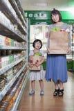 Mãe e filha que guardaram sacos de mantimento no supermercado, Pequim imagens de stock
