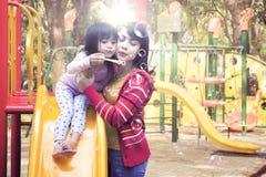 Mãe e filha que jogam bolhas de sabão no campo de jogos fotos de stock royalty free