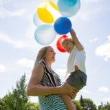Mãe e filha que jogam com os balões contra imagens de stock
