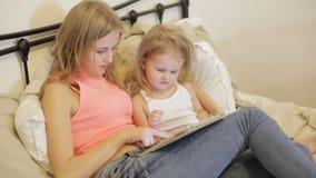 Mãe e filha que jogam com tabuleta vídeos de arquivo