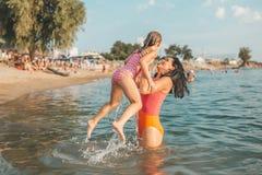 Mãe e filha que jogam na água fotografia de stock royalty free