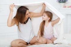 Mãe e filha que jogam na cama Imagem de Stock