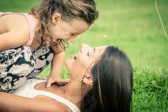 Mãe e filha que jogam na grama no tempo do dia Fotos de Stock