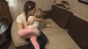 Mãe e filha que jogam na intimidação do sofá e do tapete vídeos de arquivo