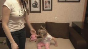 Mãe e filha que jogam na intimidação do sofá e do tapete video estoque
