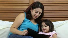 Mãe e filha que leem um livro eletrônico no quarto vídeos de arquivo