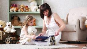 Mãe e filha que leem um livro, jogando, tendo o divertimento, abraçando, junto, 4k vídeos de arquivo