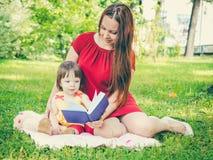 Mãe e filha que leem um livro no parque imagens de stock royalty free