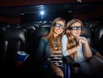 Mãe e filha que olham o filme 3D no teatro Imagem de Stock