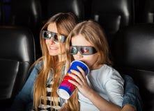 Mãe e filha que olham o filme 3D no teatro Fotos de Stock Royalty Free