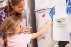 Mãe e filha que põem a estrela sobre a carta da recompensa foto de stock