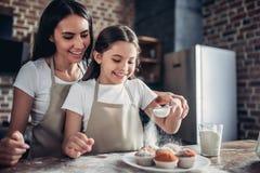 A mãe e a filha que polvilham com o açúcar pulverizam queques fotos de stock