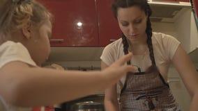 Mãe e filha que preparam o alimento na cozinha vídeos de arquivo