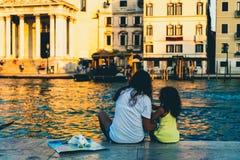 Mãe e filha que relaxam em um por do sol em Veneza, Itália fotos de stock royalty free