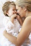 Mãe e filha que relaxam na cama imagens de stock