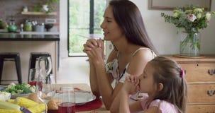 Mãe e filha que rezam antes de ter a refeição na mesa de jantar 4k vídeos de arquivo