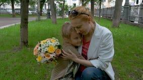 Mãe e filha que riem e que abraçam no parque do verão na grama video estoque