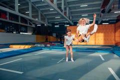 Mãe e filha que saltam no trampolim e que fazem a separação Fotos de Stock