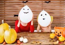 A mãe e a filha que sentam-se atrás de uma tabela no Dia das Bruxas decoraram a sala, jogando com os balões do caráter do fantasm imagem de stock