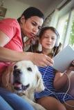 Mãe e filha que sentam-se com cão de estimação e utilização digital foto de stock royalty free
