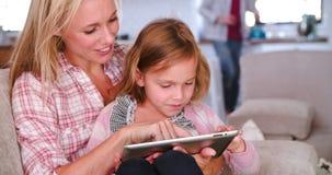 Mãe e filha que sentam-se em Sofa Using Digital Tablet filme