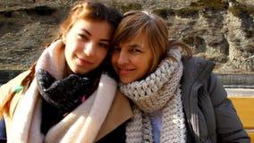 Mãe e filha que sentam-se em um banco de parque junto, aperto, beijando video estoque