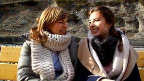 Mãe e filha que sentam-se em um banco de parque junto, aperto, beijando filme