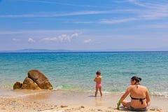 Mãe e filha que sentam-se na praia, jogando com a areia em férias de verão imagem de stock