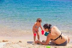 Mãe e filha que sentam-se na praia, jogando com a areia em férias de verão imagens de stock
