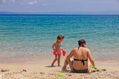 Mãe e filha que sentam-se na praia, jogando com a areia em férias de verão fotografia de stock royalty free